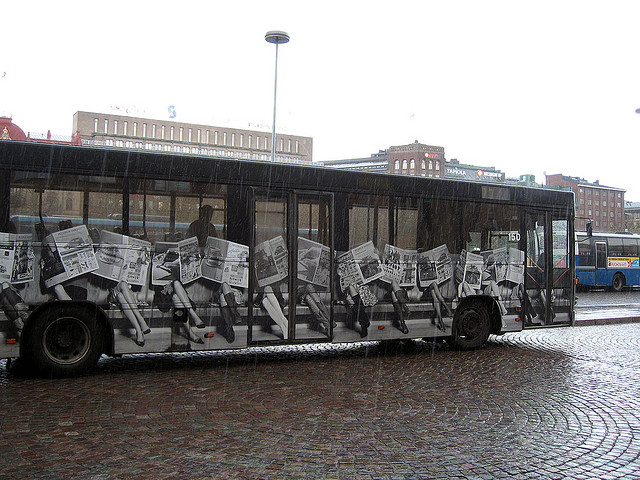 Newspaper people on bus / Helsinki 2006
