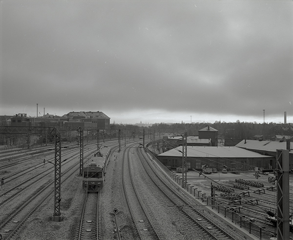 The commuter train goes to Helsinki under heavy cloud in December. The veiw from Pasilan silta,